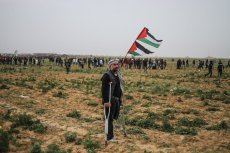 """A Palestinian man stands with a Palestinian flag as Israeli forces clash with demonstrators during a """"Great March of Return"""" demonstration at Huzaa district of Khan Yunis, Gaza on February 15, 2019. ( Mustafa Hassona - Anadolu Agency )"""