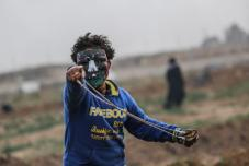 "Palestinians use sling shot to throw rocks as Israeli forces intervene them during a ""Great March of Return"" demonstration at Huzaa district of Khan Yunis, Gaza on February 15, 2019. ( Mustafa Hassona - Anadolu Agency )"