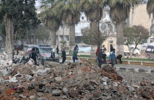 People gather around the wreckage at the site after the consecutive bomb attacks with two bomb-laden vehicles in Idlib city centre, Syria on 18 February, 2019 [Ahmet Rehhal/Anadolu Agency]