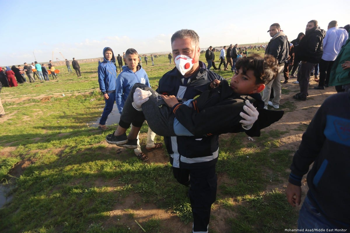 Paramedics carry an in injured child after Israeli soldiers fired at Palestinians during the Great March of Return on 8 February 2019 [Mohammed Asad/Middle East Monitor]