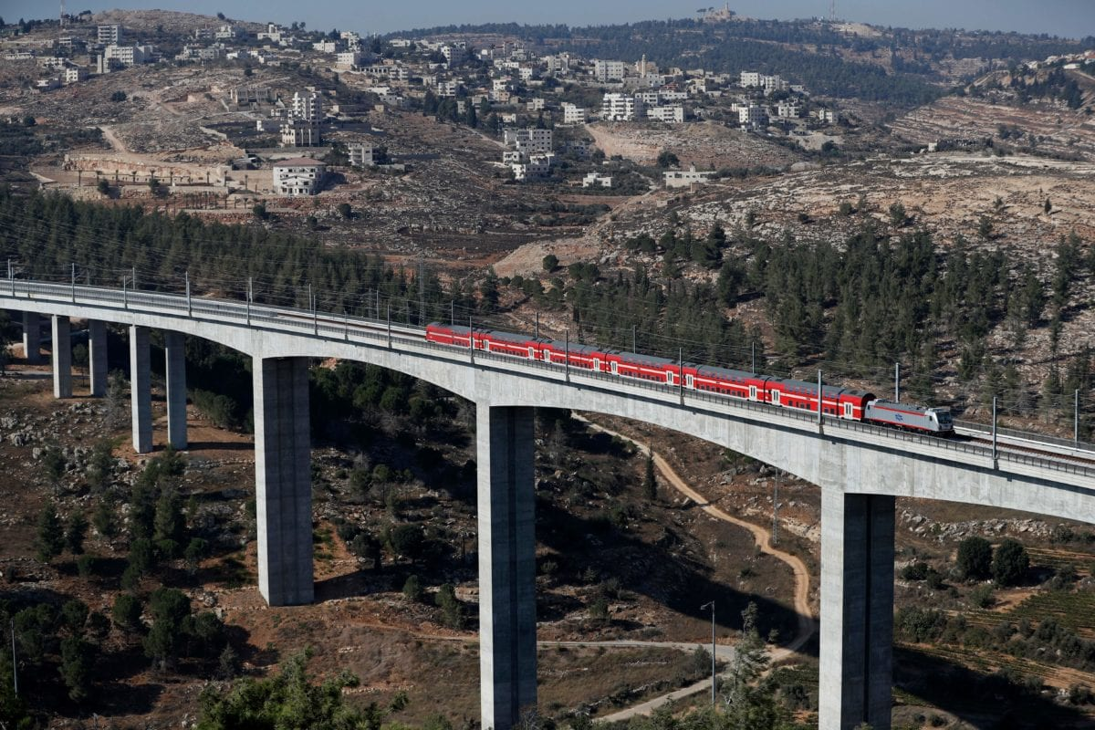 This picture taken on September 25, 2018 on the outskirts of Jerusalem shows a new high speed train travelling between Jerusalem and Israel's Ben Gurion International Airport with the Palestinian village of Beit Iksa in the background [AHMAD GHARABLI/AFP/Getty Images]