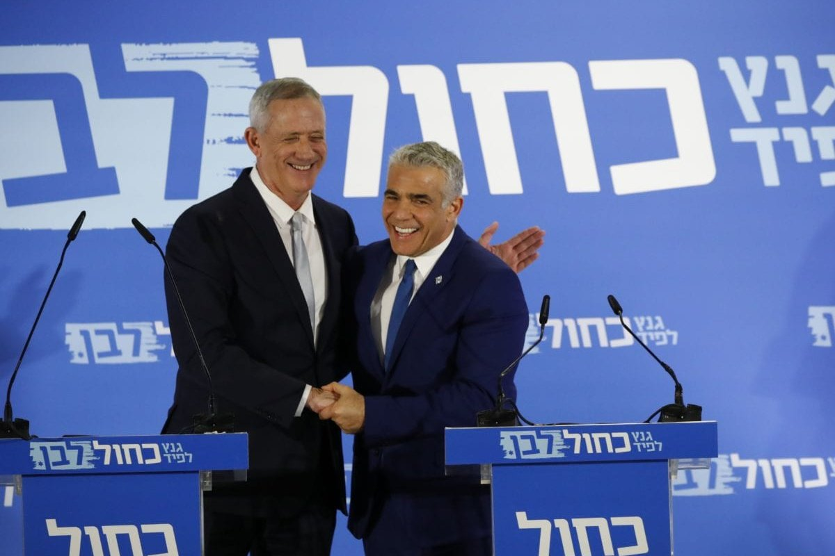 Newly allied Israeli centrist politicians, Benny Gantz (L) a former armed forces chief of staff, and Yair Lapid, react as they deliver a joint statement in the coastal city of Tel Aviv on 21 February 2019, ahead of the April 9 general election. [GUEZ/AFP/Getty Images]