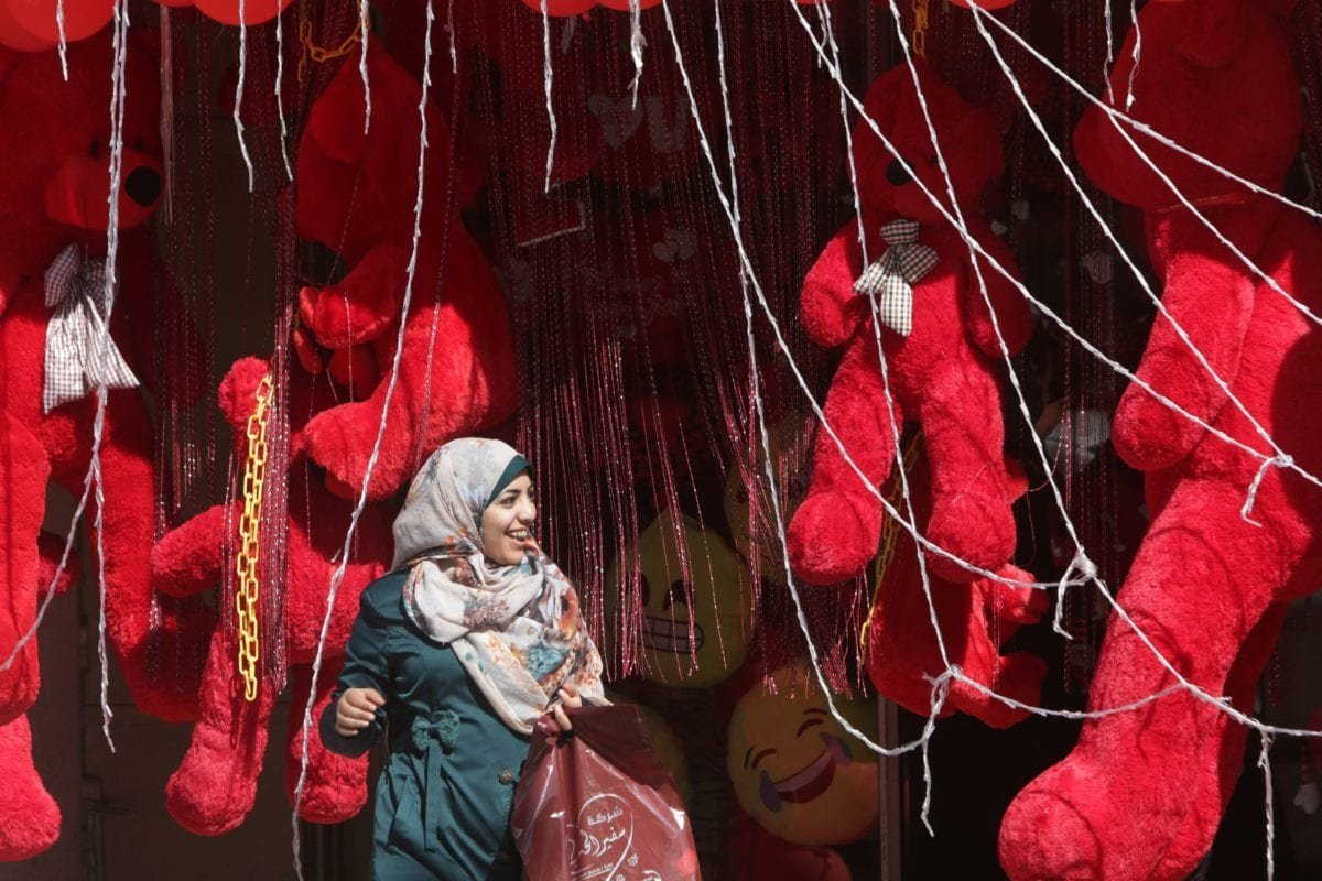 A Palestinian woman leaves a shop displaying red teddy bears on Valentine's Day on February 14, 2016 in Gaza City. / AFP / MAHMUD HAMS (Photo credit should read MAHMUD HAMS/AFP/Getty Images)