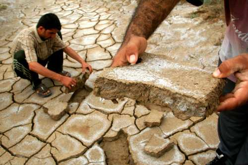 Al-Azeir, IRAQ: Iraqi men remove pieces of cracked earth from the marshes crossing the southern Iraqi town of al-Azeir, 02 April 2007. [ESSAM AL-SUDANI/AFP/Getty Images]
