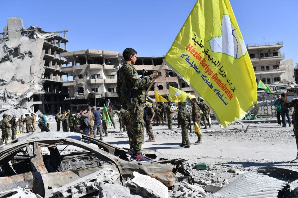 A member of the Syrian Democratic Forces (SDF), backed by US special forces, holds their flag at the iconic Al-Naim square in Raqa on 17 October, 2017 [BULENT KILIC/AFP/Getty Images]