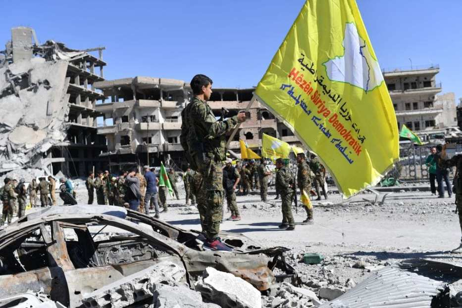 A member of the Syrian Democratic Forces (SDF), backed by US special forces, holds their flag at the iconic Al-Naim square in Raqa on October 17, 2017. [BULENT KILIC/AFP/Getty Images]