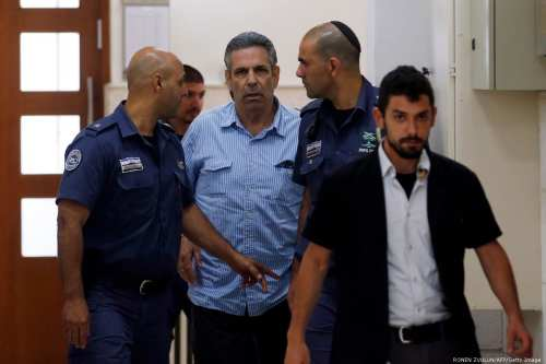 Gonen Segev, a former Israeli cabinet minister indicted on suspicion of spying for Iran, is escorted by prison guards as he arrives to court in Jerusalem on 5 July 2018 [RONEN ZVULUN/AFP/Getty Images]