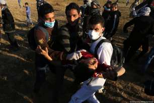 """Palestinians seen carrying away an injured protestor during a weekly """"Great March of Return"""" demonstration near the Israel-Gaza border, on March 22, 2019 [Mohammad Asad / Middle East Monitor]"""