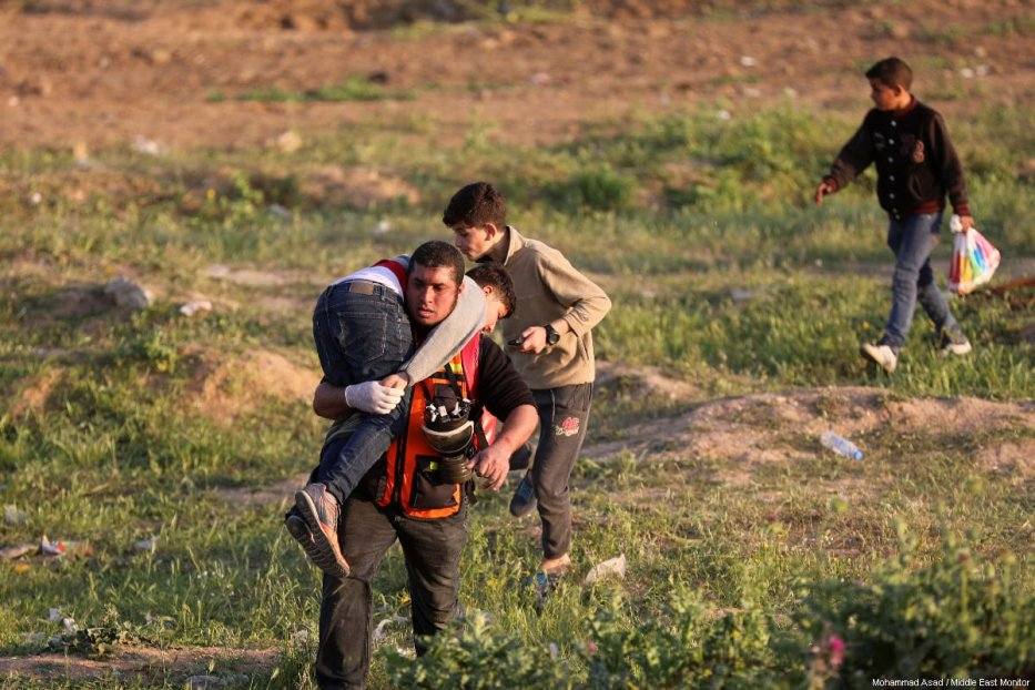 "A Palestinian medic carries away an injured protestor during a weekly ""Great March of Return"" demonstration near the Israel-Gaza border, on March 22, 2019 [Mohammad Asad / Middle East Monitor]"