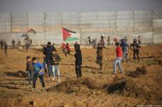 "Palestinian protestors seen near a section of the Israeli border fence, during a weekly ""Great March of Return"" demonstration near the Israel-Gaza border, on March 22, 2019 [Mohammad Asad / Middle East Monitor]"
