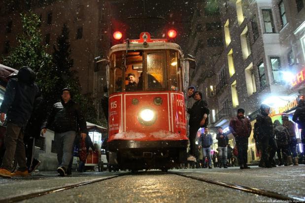 A nostalgic tramway runs inside snow covered Istiklal Avenue during the snowfall in Taksim neighbourhood of Beyoglu District, Istanbul, Turkey on 23 February 2019 [Orhan Akkanat/Anadolu Agency]