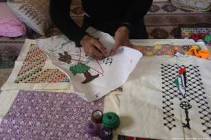 Suleiman Abu Taima uses embroidery to portray Palestinian heritage on 11 March 2019 [Mohammed Asad/Middle East Monitor]