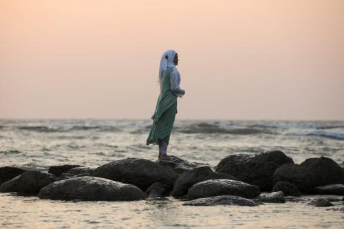 A woman watches sunset on a beach near Cox's Bazar, Bangladesh on 15 December 2017. [REUTERS/Marko Djurica ]