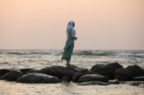 A woman watches sunset on a beach near Cox's Bazar, Bangladesh on 15 December 2017. [REUTERS/Marko Djurica ]