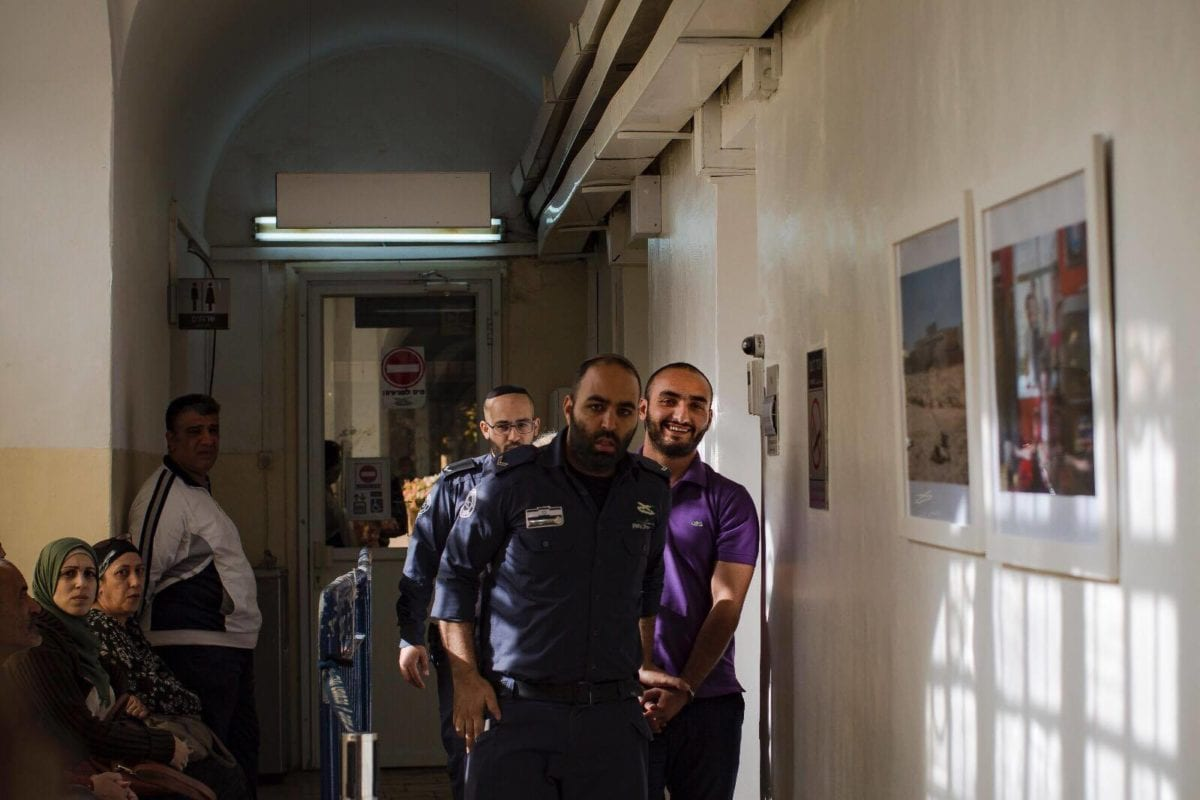 Anadolu Agency photojournalist Mostafa Al-Kharouf (R) is being brought to Israeli Magistrates' Court allegedly for not holding a residence permit in West Jerusalem on February 26, 2019 [Faiz Abu Rmeleh / Anadolu Agency]