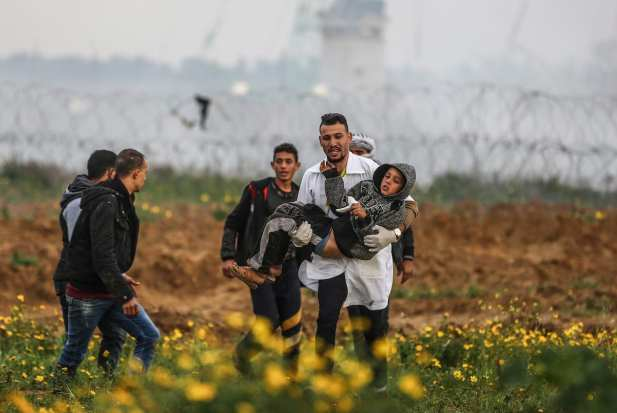 "An injured Palestinian kid is carried away after Israeli forces' clashed with protestors during a ""Great March of Return"" demonstration near Israel-Gaza border, in Khan Yunis, Gaza on March 01, 2019 [Mustafa Hassona / Anadolu Agency]"