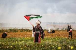 "A Palestinian woman waves a Palestinian flag during ""Great March of Return"" demonstration near Israel-Gaza border, in Khan Yunis, Gaza on March 01, 2019. ( Mustafa Hassona - Anadolu Agency )"