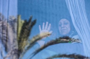 A woman waves hand as she and others from the first convoy pass the Rafah Border Gate to transport and perform Umrah in Mecca after Egypt re-opened the Rafah Crossing following four years of closure, in Rafah, Gaza on March 03, 2019 [Ali Jadallah / Anadolu Agency]