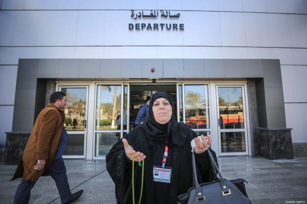 A woman from the first convoy, passes through the Rafah Border Gate and waits to transport and perform Umrah in Mecca after Egypt re-opened the Rafah Border Gate following four years of closure, in Rafah, Gaza on March 03, 2019 [Ali Jadallah / Anadolu Agency]