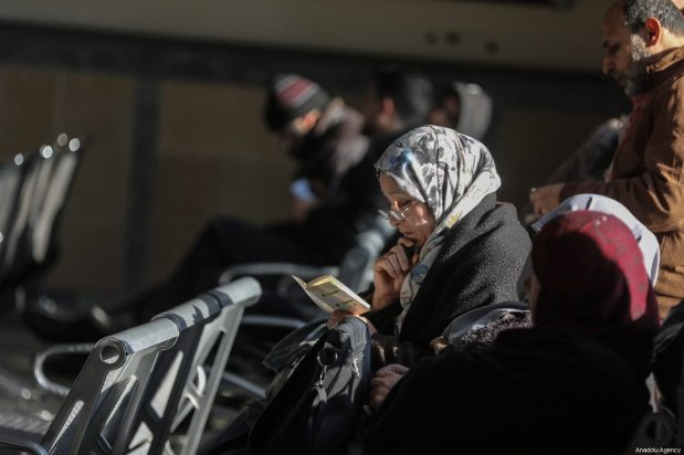 A woman from the first convoy passes the Rafah Border Gate and recites from the holy Quran as she waits to transport and perform Umrah in Mecca after Egypt re-opened the Rafah Crossing following four years of closure, in Rafah, Gaza on March 03, 2019 [Ali Jadallah / Anadolu Agency]