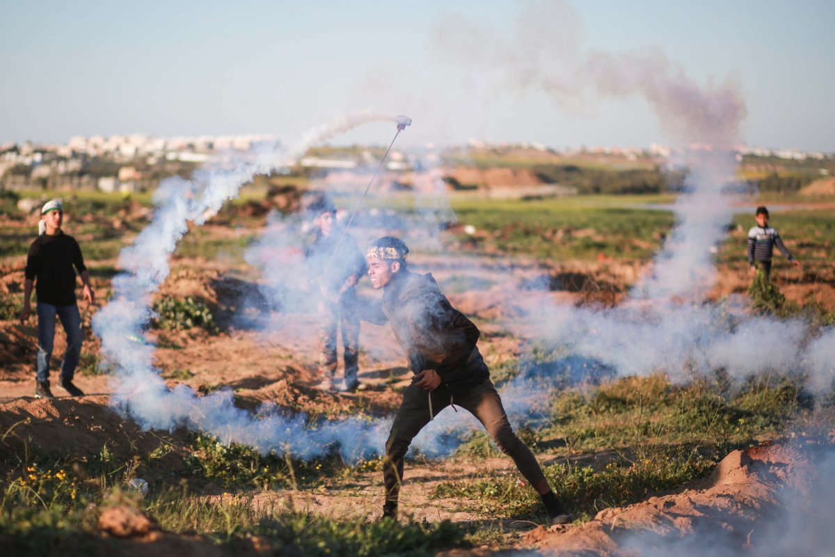 """A Palestinian throws tear gas cannister back to Israeli forces during a""""Great March of Return"""" demonstration near Al Bureij Refugee Camp in Gaza City, Gaza on 8 March, 2019 [Hassan Jedi/Anadolu Agency]"""