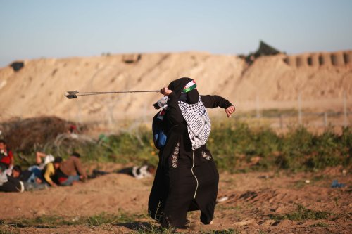 """A Palestinian woman uses slingshot to throw stone to Israeli forces during a""""Great March of Return"""" demonstration near Al Bureij Refugee Camp in Gaza City, Gaza on 8 March, 2019 [Hassan Jedi/Anadolu Agency]"""