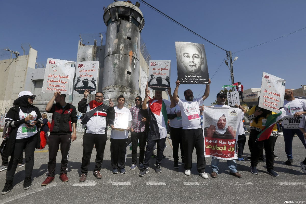 A group of people stage a demonstration in front of the Israel's West Bank separation wall to show their support to the Palestinian prisoners in Bethlehem, West Bank on 22 March 2019 [Wisam Hashlamoun/Anadolu Agency]