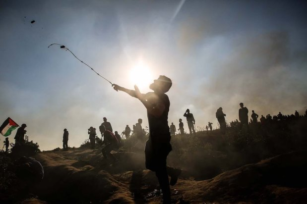 "A Palestinian throws rock in response to Israeli forces' intervention during a protest within ""Great March of Return"" demonstrations near Al Bureij Refugee Camp in Gaza City, Gaza on March 22, 2019. ( Hassan Jedi - Anadolu Agency )"
