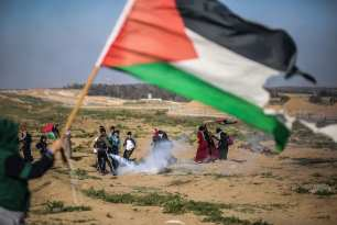 """Israeli forces intervene Palestinians with tear gas during a protest within """"Great March of Return"""" demonstrations near Al Bureij Refugee Camp in Gaza City, Gaza on March 22, 2019. ( Hassan Jedi - Anadolu Agency )"""