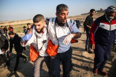 """An injured medical staff is being carried away after Israeli forces' intervention during a protest within """"Great March of Return"""" demonstrations near Al Bureij Refugee Camp in Gaza City, Gaza on March 22, 2019. ( Hassan Jedi - Anadolu Agency )"""