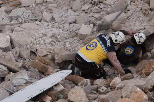 Civil defense members conduct a search and rescue operation under the rubbles of demolished buildings after airstrikes hit the residential areas of de-escalation zone Idlib, Syria on 22 March 2019. [Hasan Muhtar - Anadolu Agency]