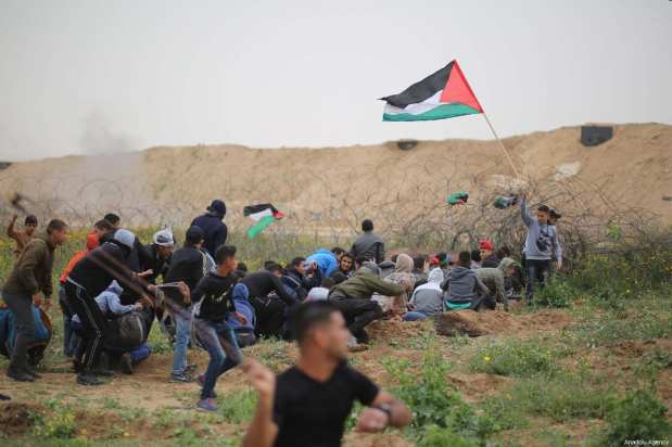 """Palestinians throw rocks in response to Israeli tear gas fire, at the anniversary march of the """"Great March of Return"""" and """"Palestinian Land Day"""" protests at Israel-Gaza border located near Al Bureij Refugee Camp in Gaza City, Gaza on March 30, 2019 [Hassan Jedi / Anadolu Agency]"""