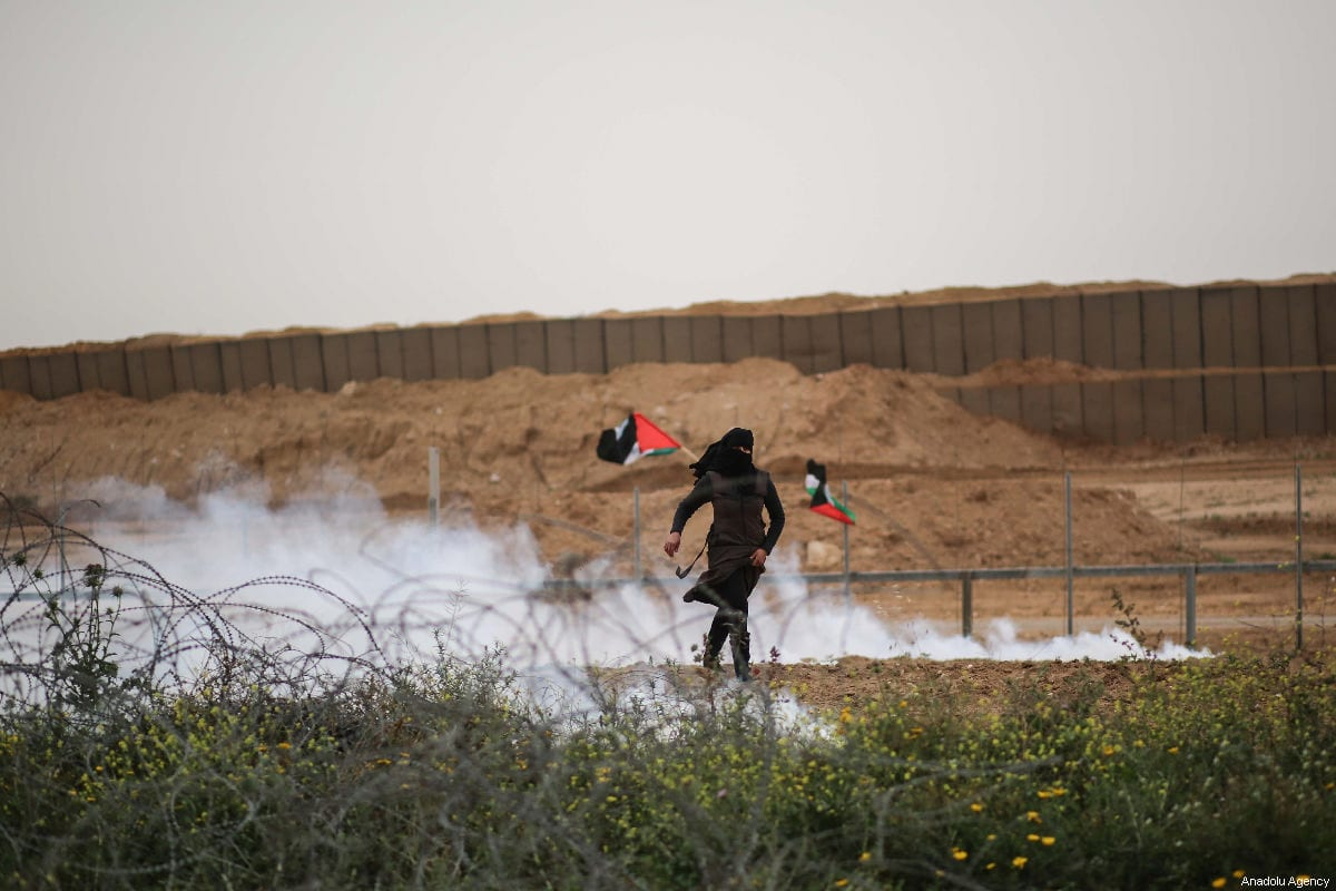 """Israeli forces shoot multiple tear gas canisters at a Palestinian woman with during the anniversary march of the """"Great March of Return"""" and """"Palestinian Land Day"""" protests at Israel-Gaza border located near Al Bureij Refugee Camp in Gaza City, Gaza on March 30, 2019 [Hassan Jedi / Anadolu Agency]"""