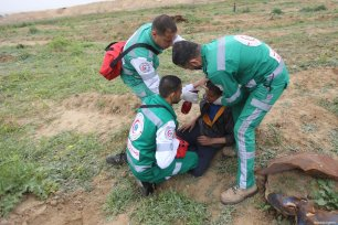 """Palestinian medical staff treat a Palestinian, affected by tear gas, during the anniversary march of the """"Great March of Return"""" and """"Palestinian Land Day"""" protests at Israel-Gaza border located near Al Bureij Refugee Camp in Gaza City, Gaza on March 30, 2019 [Hassan Jedi / Anadolu Agency]"""