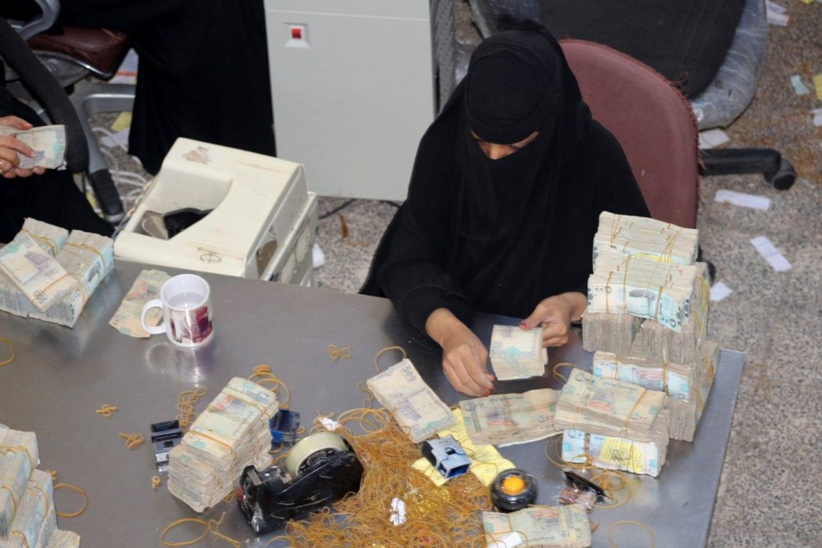 A bank teller counts money at the Central Bank of Aden in Aden on December 13, 2018 [Saleh Al-OBEIDI / AFP / Getty]
