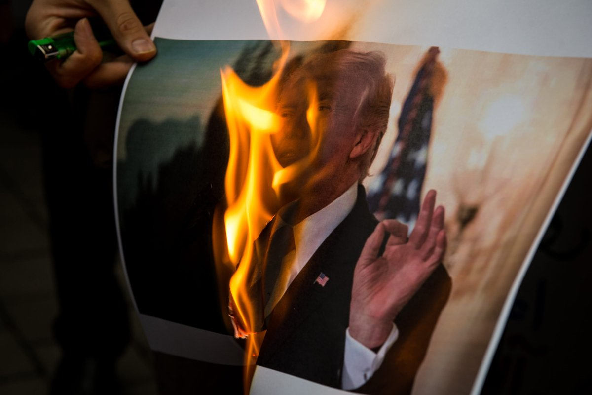 Iranian demonstrators burn a picture of the US President Donald Trump during a protest in front of the former US Embassy on 9 May, 2018 in Tehran, Iran [Majid Saeedi/Getty Image]