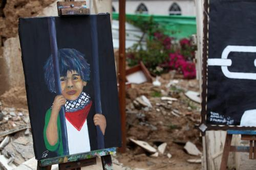 "Palestinians attend the opening of the exhibition ""From the Rubble"" marking Palestinian Prisoner Day at the Arts and Crafts Village that was damaged in an Israeli airstrike on the Gaza City on 17 April, 2019 [Mahmoud Ajjour/Apaimages]"
