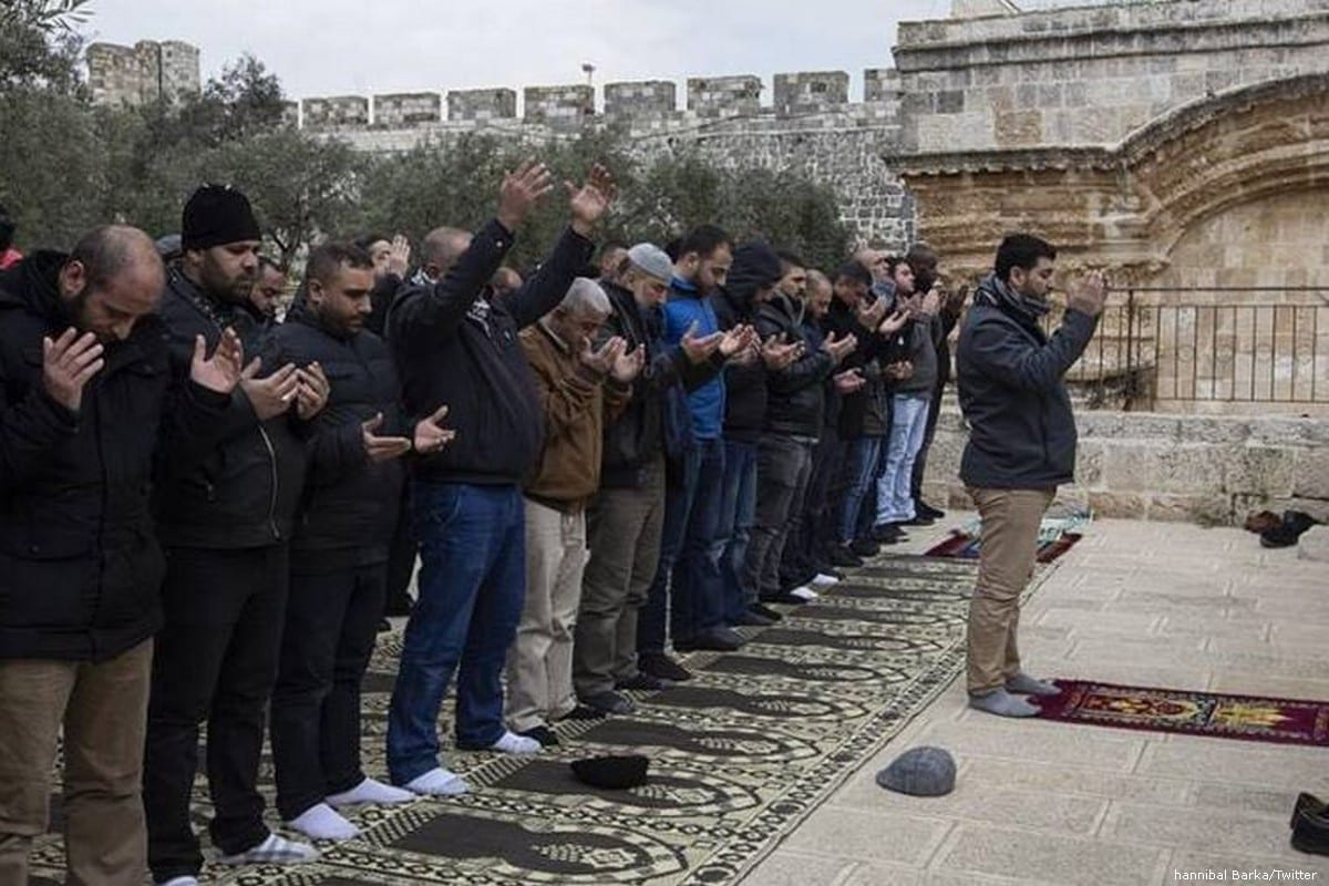 Palestinians perform prayer in front of Al-Rahma Gate (Gate of Mercy) of Al-Aqsa Mosque Compound, as Israeli security forces stand guard behind them after Al-Rahma Gate was chained by Israeli police in Jerusalem on 22 February 2019 [hannibal Barka/Twitter]