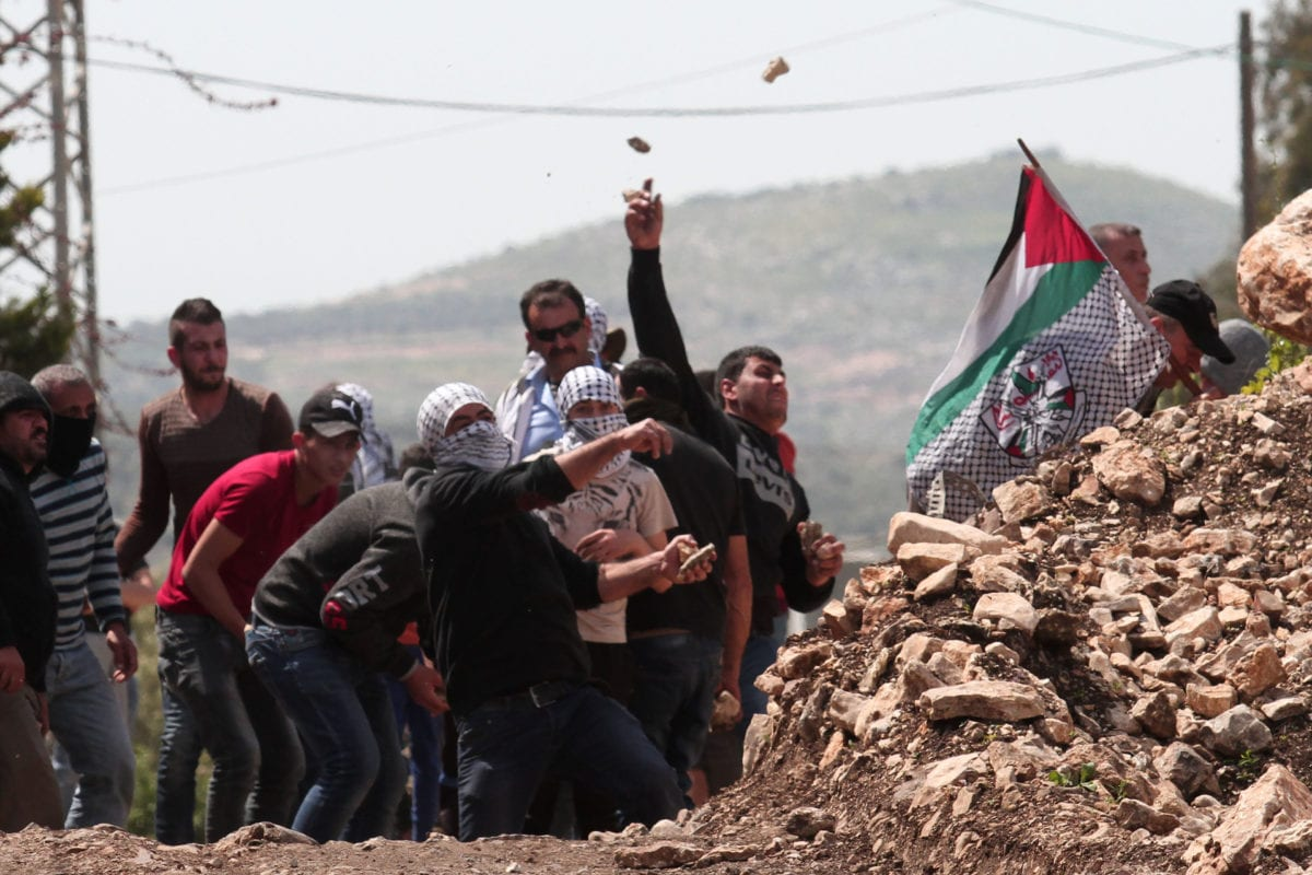 Palestinians throw stones with slingshots in response to Israeli forces' intervention during a protest against building of Jewish settlements and separation wall at Kafr Qaddum village of Nablus, West Bank on 12 April 2019. [Nedal Eshtayah - Anadolu Agency]