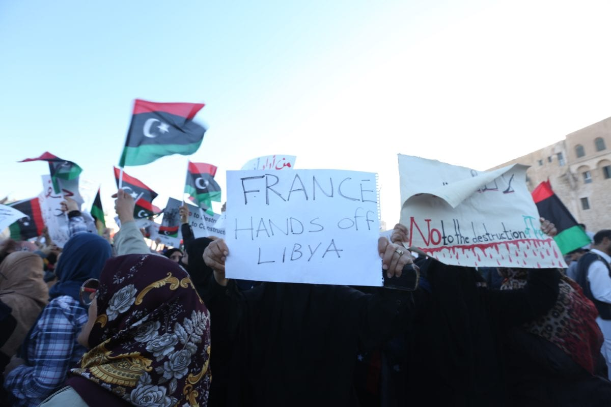 """A protestor carries a banner reading """"France hands off Libya"""" during a protest against Libyan military commander Khalifa Haftar's offensive to seize Tripoli, on 12 April 2019. [Hazem Turkia - Anadolu Agency]"""