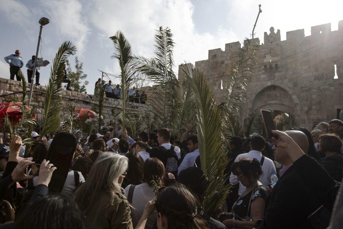 Orthodox Christians take part in the parade in front of Al Esbat Gate of the Jerusalem's Old City during 'Palm Sunday' celebrations in Jerusalem on 14 April 2019. [Faiz Abu Rmeleh - Anadolu Agency]