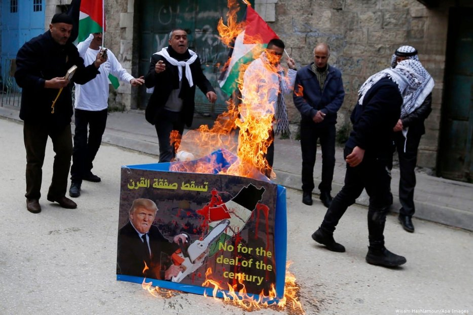 Palestinian protestors burn a poster with a picture of US President Donald Trump during a demonstration against the deal of century, in the West Bank city of Hebron, 22 February 2019 [Wisam Hashlamoun/Apa Images]