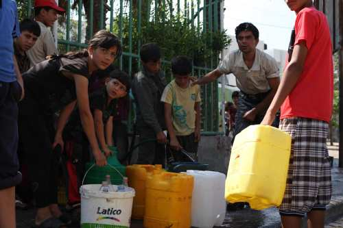 Palestinians children fill plastic bottles and water containers with drinking water from a public tap in Jabalia in the northern Gaza Strip on July 27, 2014. [Ashraf Amra/ApaImages]