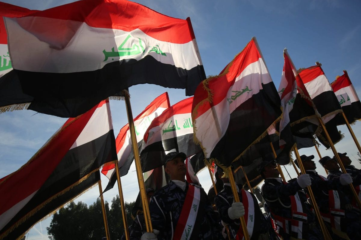 Iraqi policemen hold their national flag and march during a parade in Baghdad on 10 January 2019 to mark the graduation of 158 Iraqi policemen after a six-month training period. [AHMAD AL-RUBAYE / AFP / Getty]