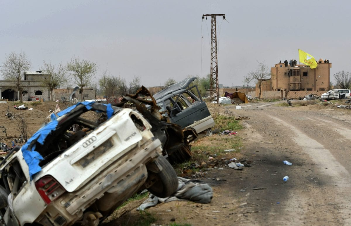 """This picture shows destroyed vehicles lying in a ditch on the side of a road with the Syrian Democratic Forces (SDF) unfurled flag seen flying on a roof in the background surrounded by SDF fighters in the village of Baghouz in Syria's eastern Deir Ezzor province near the Iraqi border, a day after the Islamic State (IS) group's """"caliphate"""" was declared defeated by the US-backed Kurdish-led SDF on 24 March 2019 [GIUSEPPE CACACE / AFP / Getty]"""