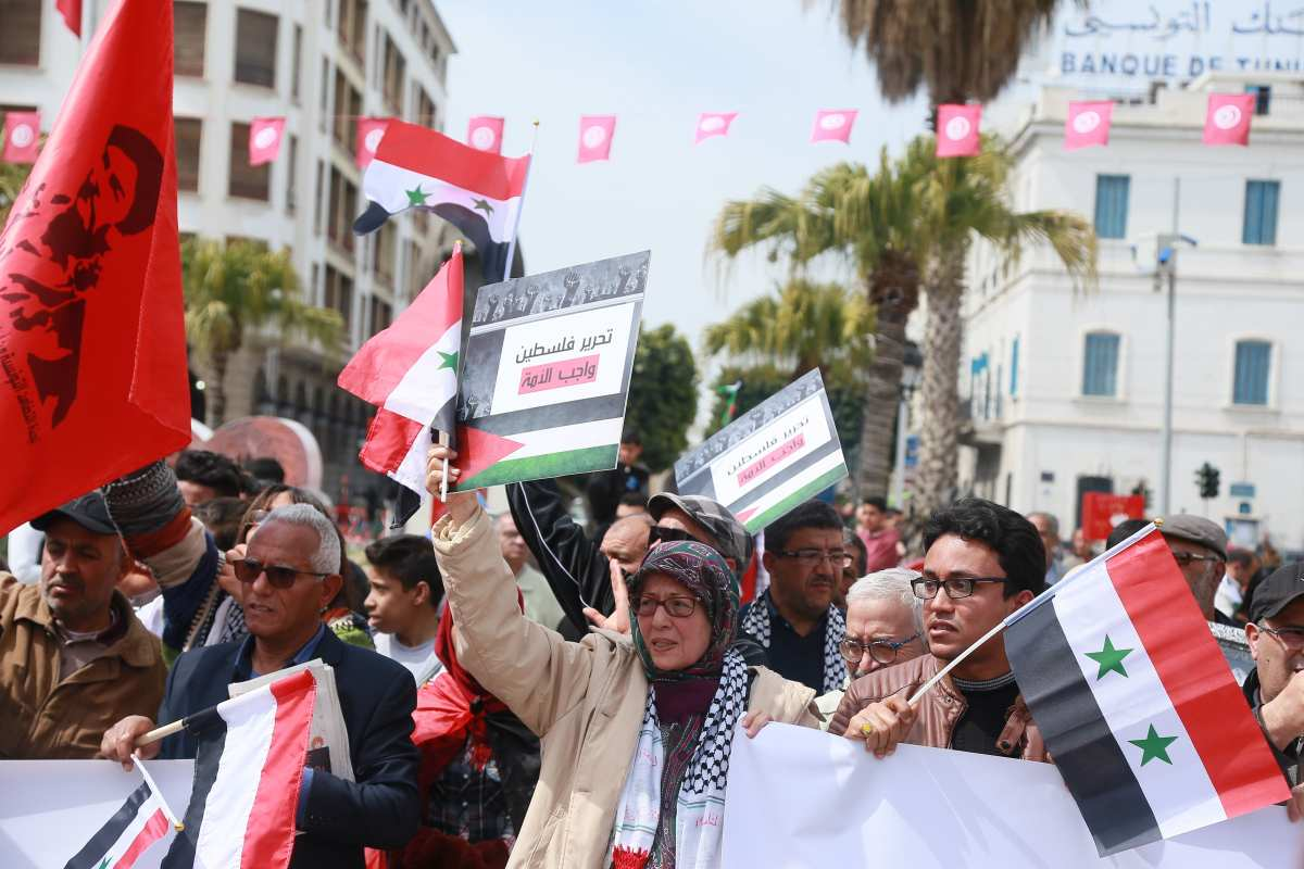 Tunisians hold the Syrian and Palestinian flags as they demonstrate against the Arab League Summit and the United States recognition of Israeli sovereignty over the Golan Heights, on Habib Bourguiba Avenue in the capital Tunis on 31 March, 2019 [ANIS MILI/AFP/Getty]