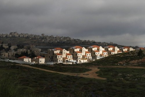 The illegal Jewish settlement of Neve Yaakov (foreground) in the northern area of east Jerusalem and Israel's controversial barrier separating the Palestinian neighbourhood of al-Ram (background) in the West Bank, on April 1, 2019. [AHMAD GHARABLI / AFP / Getty]