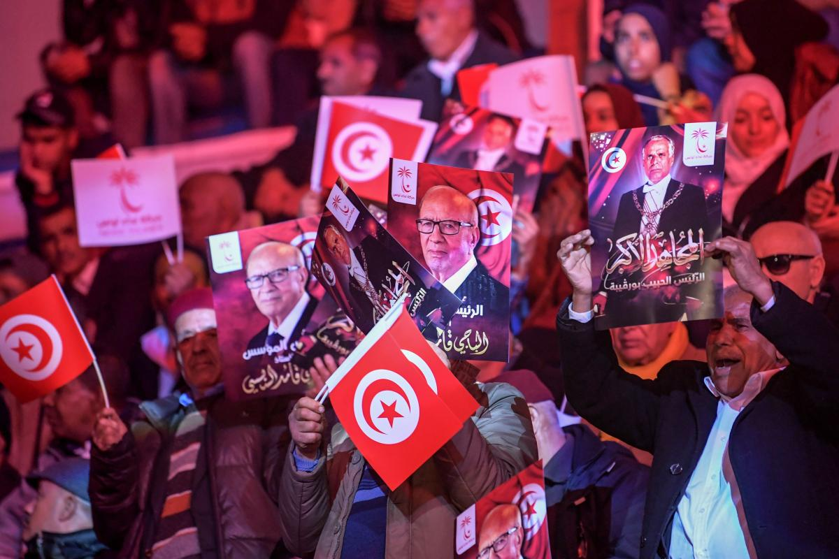 Supporters of Tunisian President Beji Caid Essebsi wave posters depicting his portrait in Tunis, Tunisia on 6 April 2019 [FETHI BELAID/AFP/Getty]