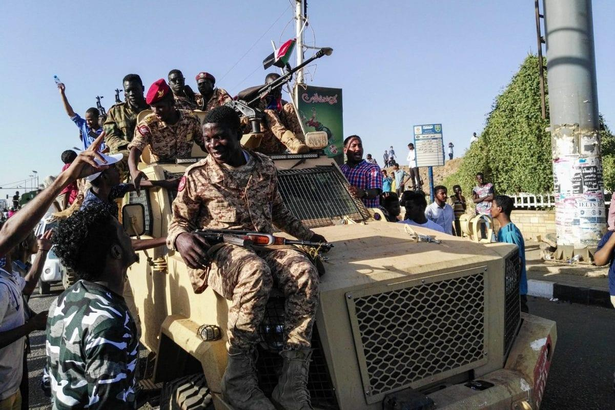 Sudanese protesters sit atop a military vehicle in Khartoum, Sudan on 7 April 2019 [AFP/Getty]