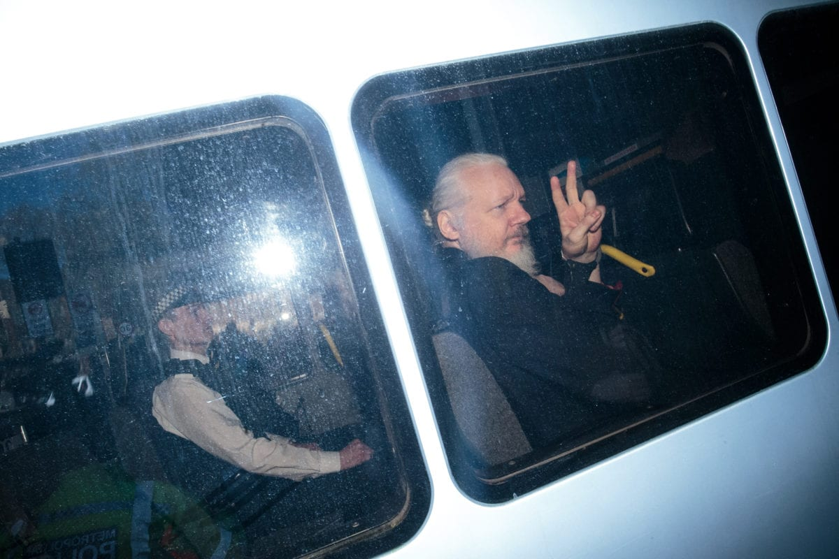 Julian Assange gestures to the media from a police vehicle on his arrival at Westminster Magistrates court on April 11, 2019 in London, England. [Jack Taylor/Getty Images]